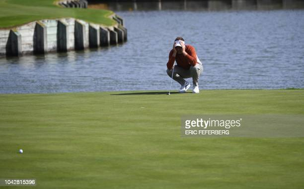 Europe's English golfer Ian Poulter lines up a putt during his fourball match on the second day of the 42nd Ryder Cup at Le Golf National Course at...