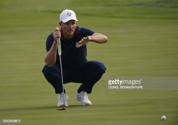Europe's English golfer Justin Rose gestures as he lines up a putt during his foursomes match on the first day of the 42nd Ryder Cup at Le Golf...