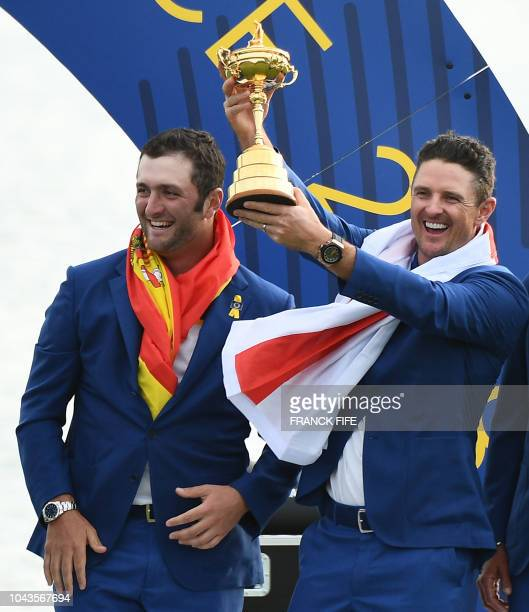 TOPSHOT Europe's English golfer Justin Rose holds the trophy next to Europe's Spanish golfer Jon Rahm after Europe won the 42nd Ryder Cup at Le Golf...