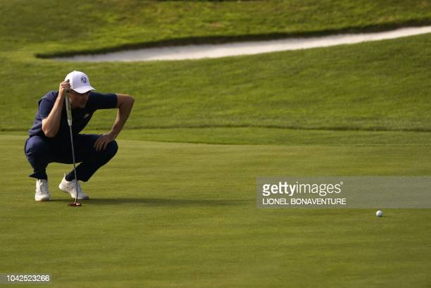 TOPSHOT Europe's English golfer Justin Rose lines up a putt during his foursomes match on the first day of the 42nd Ryder Cup at Le Golf National...