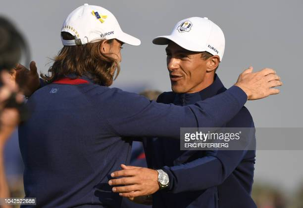 Europe's English golfer Tommy Fleetwood celebrates with Europe's Danish golfer Thorbjorn Olesen after winning his foursomes match on the first day of...