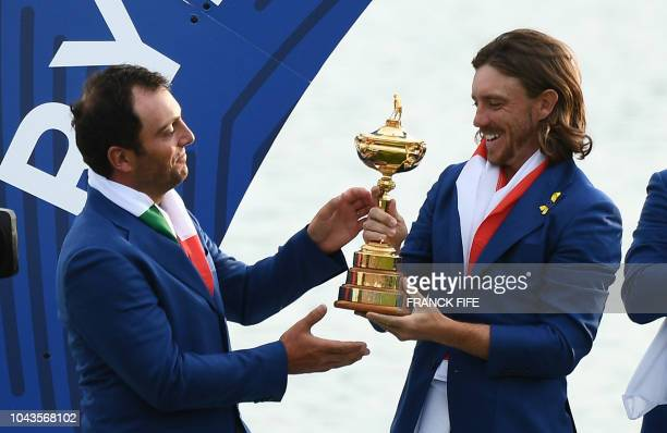 Europe's English golfer Tommy Fleetwood Italian golfer Francesco Molinari hold the trophy as they celebrate winning the 42nd Ryder Cup at Le Golf...