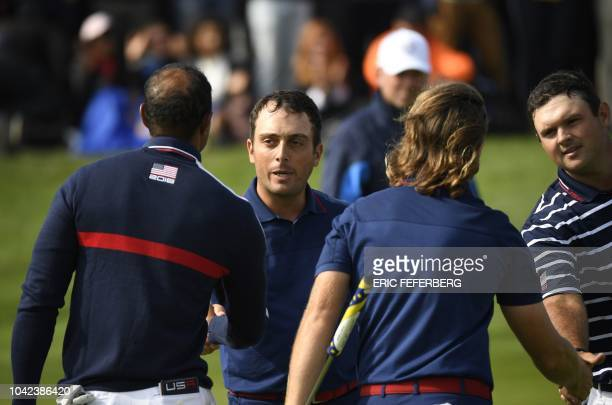 Europe's English golfer Tommy Fleetwood shakes hands with US golfer Patrick Reed and US golfer Tiger Woods as he celebrates his victory with Europe's...