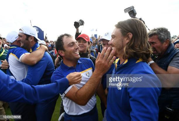 TOPSHOT Europe's Italian golfer Francesco Molinari celebrates with Europe's English golfer Tommy Fleetwood after victory in during his singles match...