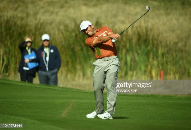 Europe's Italian golfer Francesco Molinari plays a fairway shot his foursomes match on the second day of the 42nd Ryder Cup at Le Golf National...