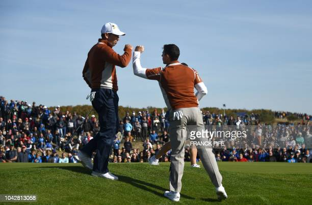 Europe's Northern Irish golfer Rory McIlroy celebrates with Europe's Spanish golfer Sergio Garcia during their fourball match on the second day of...