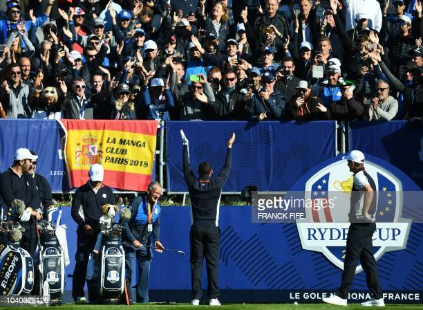 Europe's Northern Irish golfer Rory McIlroy gestures to spectators during a practice session ahead of the 42nd Ryder Cup at Le Golf National Course...