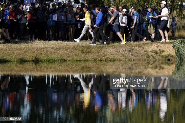 Europe's Northern Irish golfer Rory McIlroy is reflected in water as he walks during a practice session ahead of the 42nd Ryder Cup at Le Golf...