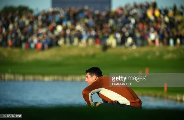Europe's Northern Irish golfer Rory McIlroy lines up a shot during his fourball match on the second day of the 42nd Ryder Cup at Le Golf National...