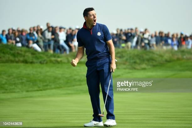 TOPSHOT Europe's Northern Irish golfer Rory McIlroy reacts after making a putt during his foursomes match on the first day of the 42nd Ryder Cup at...