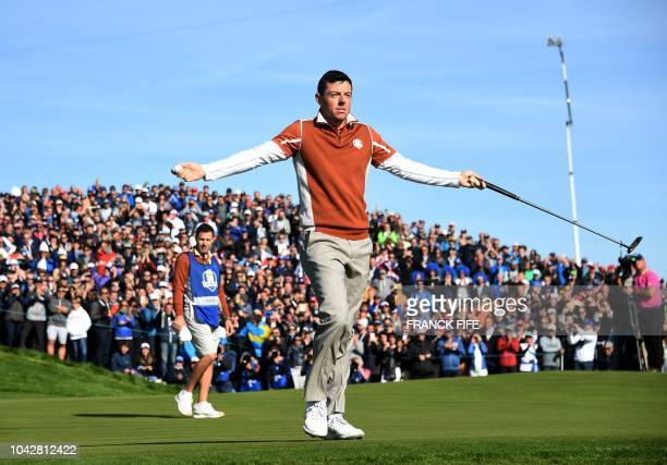 Europe's Northern Irish golfer Rory McIlroy reacts during his fourball match on the second day of the 42nd Ryder Cup at Le Golf National Course at...