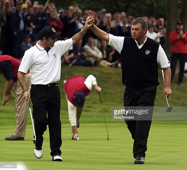 Europe's Paul McGinley of Ireland and Darren Clarke of Northern Ireland celebrate on the 14th green during the afternoon fourball matches on the...
