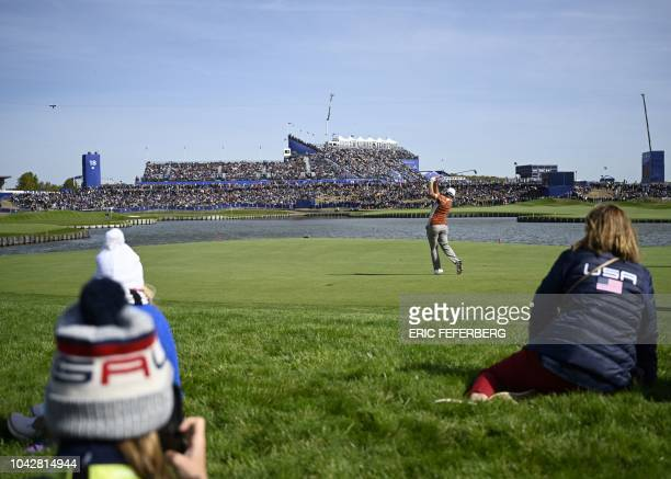 Europe's Spanish golfer Jon Rahm plays a fairway shot during his fourball match on the second day of the 42nd Ryder Cup at Le Golf National Course at...