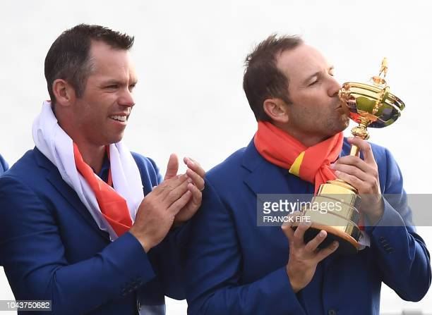 Europe's Spanish golfer Sergio Garcia kisses the trophy as Europe's English golfer Paul Casey as they celebrate winning the 42nd Ryder Cup at Le Golf...