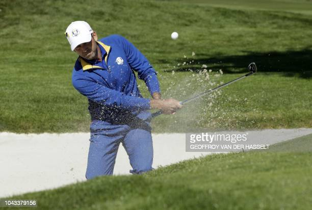 Europe's Spanish golfer Sergio Garcia plays a shot out of a bunker during his singles match with US golfer Rickie Fowler on the third day of the 42nd...