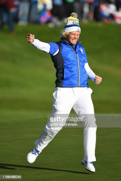 Europe's Suzann Pettersen celebrates after winning her tie on the 18th green in the singles on the third day of The Solheim Cup golf tournament at...