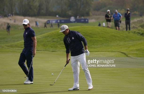 Europe's Swedish golfer Henrick Stenson looks on as US golfer Rickie Fowler juggles a ball during his foursomes match on the first day of the 42nd...
