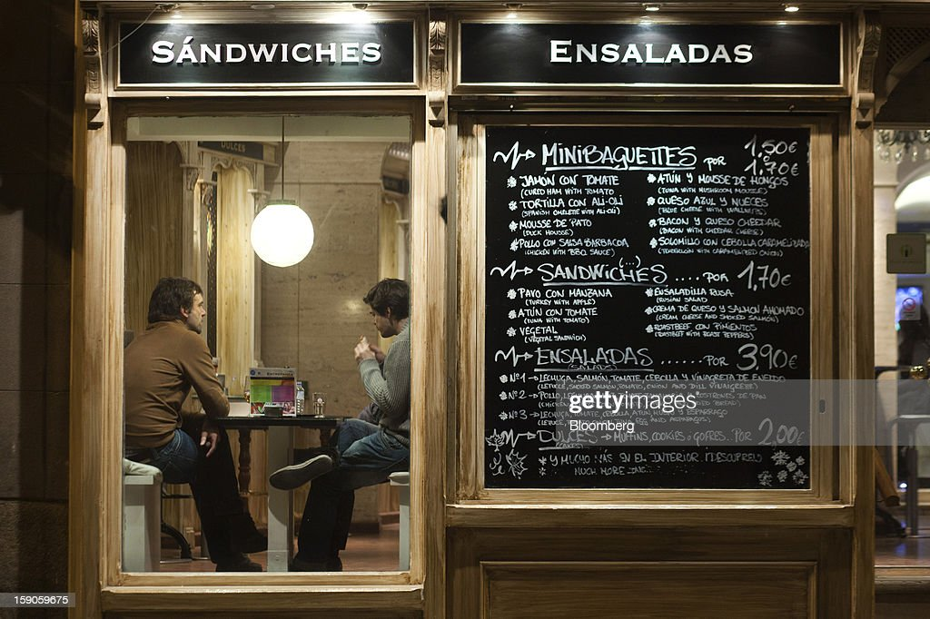 A euro-priced menu sits on display outside a cafe as customers sit and talk beneath an electric light in Madrid, Spain, on Sunday, Jan. 6, 2013. In December, the Spanish parliament passed an energy law that imposed a 7 percent tax on electricity generation from Jan. 1 to plug the deficit. Photographer: Angel Navarrete/Bloomberg via Getty Images