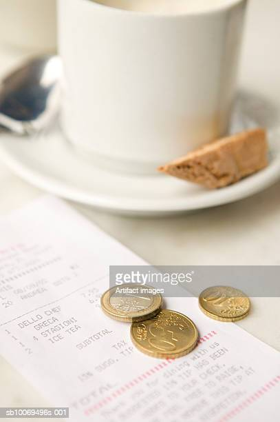 Euros coins by coffee cup and bill