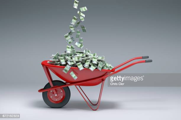 Euros falling into red wheelbarrow