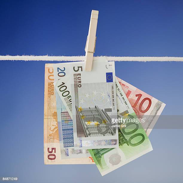 euros hanging on a clothesline - five euro banknote stock photos and pictures