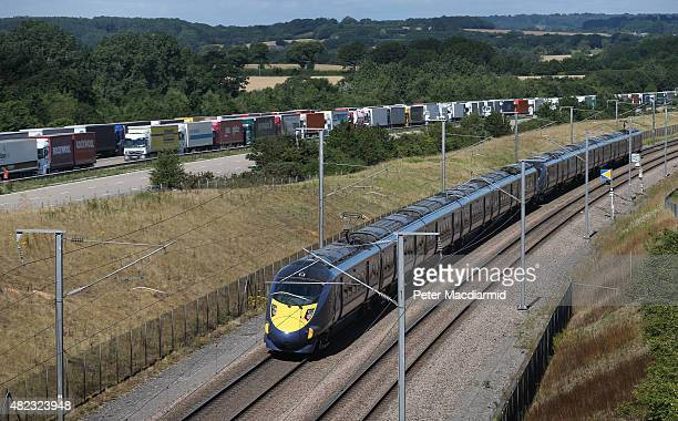 Eurostar passenger train passes trucks parked on the M20 motorway during Operation Stack on July 30 2015 near Charing England Operation stack remains...