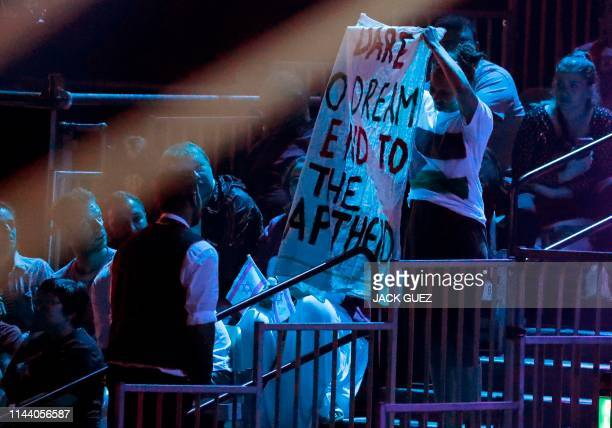 Eurovision Song Contest 2019 attendee wearing a T-shirt bearing the Palestinian flag stands while holding up a protest banner, during the second...
