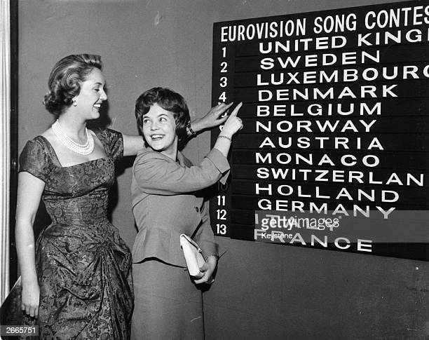 Eurovision Song Contest compere Katie Boyle checks the scoreboard for the order of the draw with Katy Bodtger of Denmark