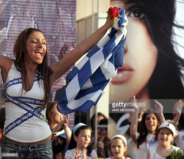 Eurovision Song Contest winner winner Helena Paparizou of Greece waves her national flag arriving in Athens 23 May 2005 About 1000 fans of the Greek...