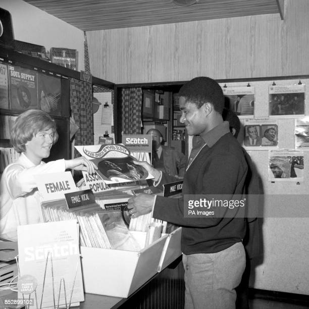 Eusebio star of Portugal's Benfica soccer team buys Otis Redding's record The Dock of the Bay at a music shop in Harlow New Town from Sally Sargeant...