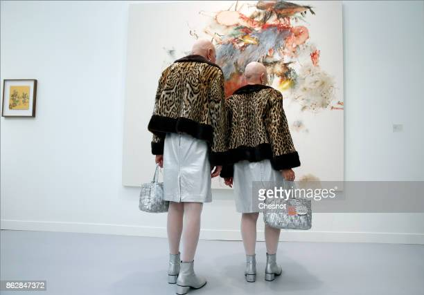 Eva and Adele selfproclaimed artists The Hermaphrodite Twins in Art look at an artwork by Indonesian artist Christine Ay Tjoe at the Grand Palais as...