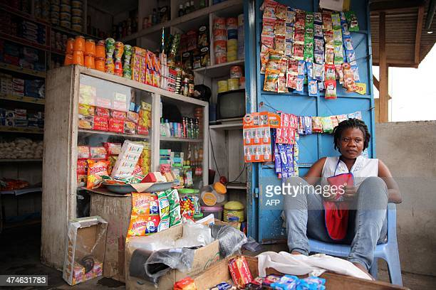 Eva Botchway sits outside her shop in Accra on February 11 2014 Botchway had to repeatedly raise her prices due to the weakening Cedi Ghana's...
