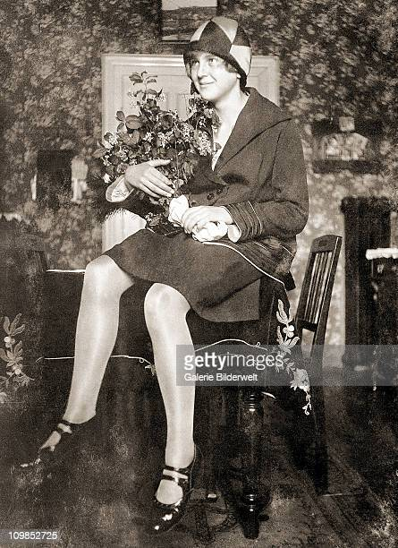Eva Braun sitting on a table in the living room at her parent's house in Munich, Germany, 1929. She was staying with her family after finishing her...