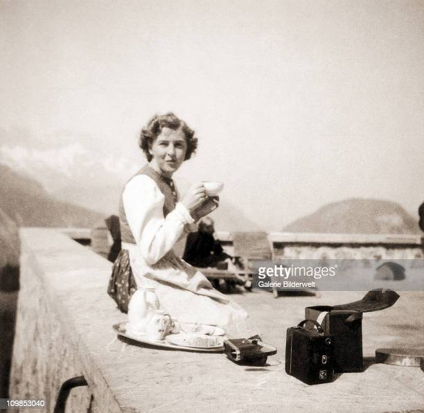 Eva Braun sitting on a terrace in a Bavarian dress, at the Berghof, Hitler's residence, near Berchtesgaden, Germany, 1942. A box camera is next to...