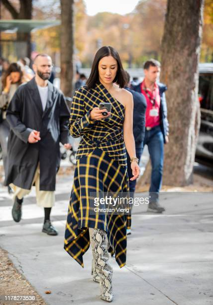 Eva Chen seen wearing navy yellow checkered ripped off dress, boots with snake print outside Sacai during Paris Fashion Week Womenswear Spring Summer...