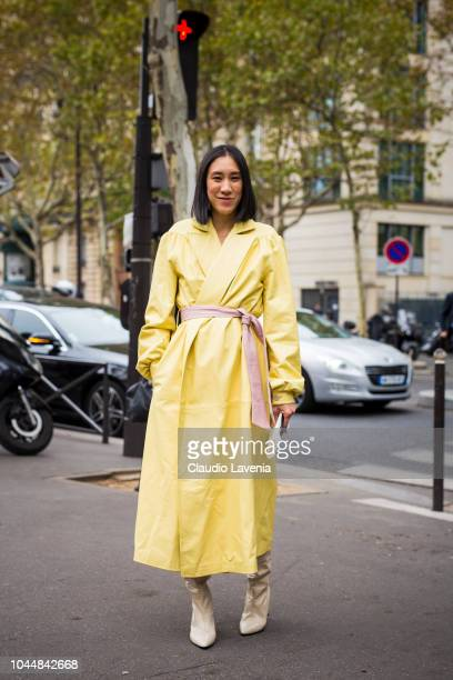 Eva Chen wearing a long yellow trench coat and beige boots is seen before the Miu Miu show on October 2 2018 in Paris France