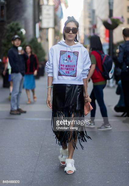 Eva Chen wearing a white hoody with the print no walls between us and a skirt with fringes seen in the streets of Manhattan outside Victoria Beckham...