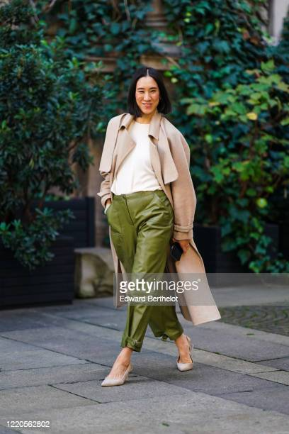 Eva Chen wears a beige long coat, a white t-shirt, green leather pants, pointy shoes, outside Koche x Pucci, during Milan Fashion Week Fall/Winter...