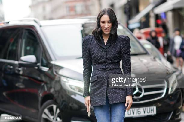 Eva Chen wears a black jacket with white printed polka dots and shoulder pads blue denim jeans white shoes during London Fashion Week February 2019...
