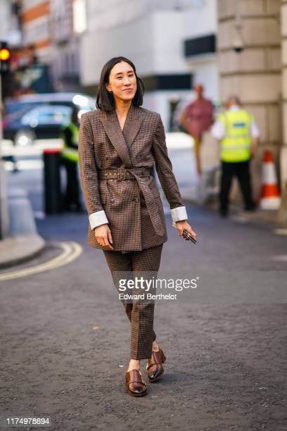 Eva Chen wears a brown checked blazer long jacket a large belt flare pants brown leather shoes during London Fashion Week September 2019 on September...