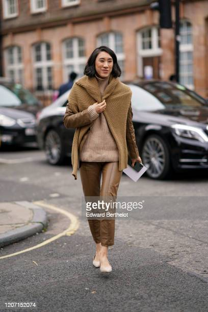 Eva Chen wears a brown wool knitted pullover over the shoulders, brown leather pants, a brown leather jacket, a beige pullover, pointy shoes, during...