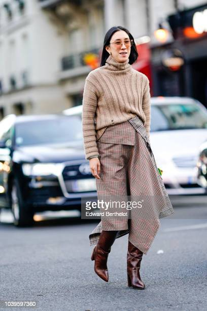 Eva Chen wears a brown wool turtleneck pullover a checked printed skirt brown leather boots outside Gucci during Paris Fashion Week Womenswear...