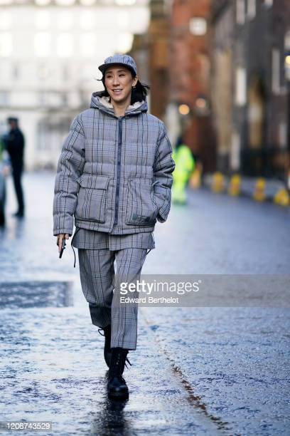 Eva Chen wears a cap a checked puffer jacket with a hood pants during London Fashion Week Fall Winter 2020 on February 16 2020 in London England