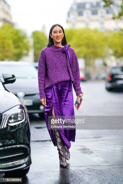 Eva Chen wears a heather purple wool top with a bow collar lined with lustrous purple satin a lustrous purple satin sideslit long skirt python...