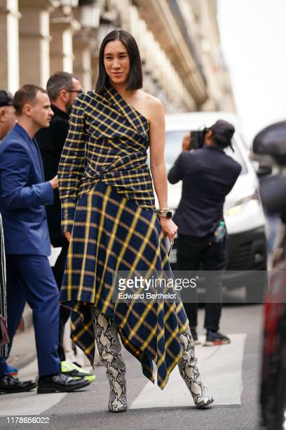 Eva Chen wears a navy blue and yellow checkered asymmetric one-shoulder dress with a handkerchief hem, grey and beige python pattern pointy boots,...