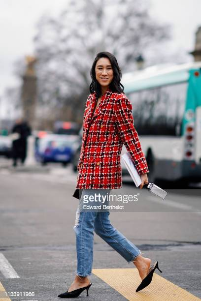 Eva Chen wears a red and black checkered tweed jacket with brass buttons ripped jeans black pointy mules outside Chanel during Paris Fashion Week...