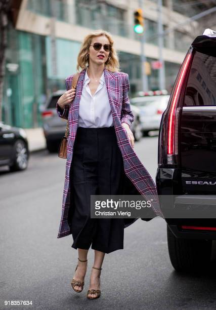 Eva Herzigova wearing plaid coat seen outside Michael Kors on February 14 2018 in New York City