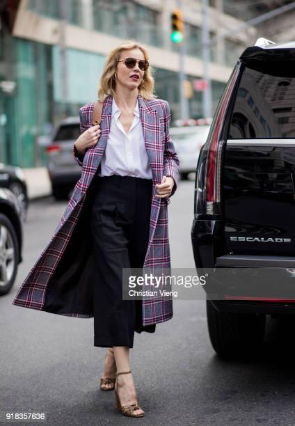 Eva Herzigova wearing plaid coat seen outside Michael Kors on February 14 2018 in New York City