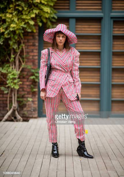 Eva Koyen wearing hat and red white plaid suit black boots bag with fringes and black bag seen during MercedesBenz Tbilisi Fashion Week on November 1...