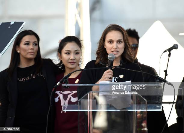 Eva Longoria Constance Wu and Natalie Portman speak onstage at 2018 Women's March Los Angeles at Pershing Square on January 20 2018 in Los Angeles...